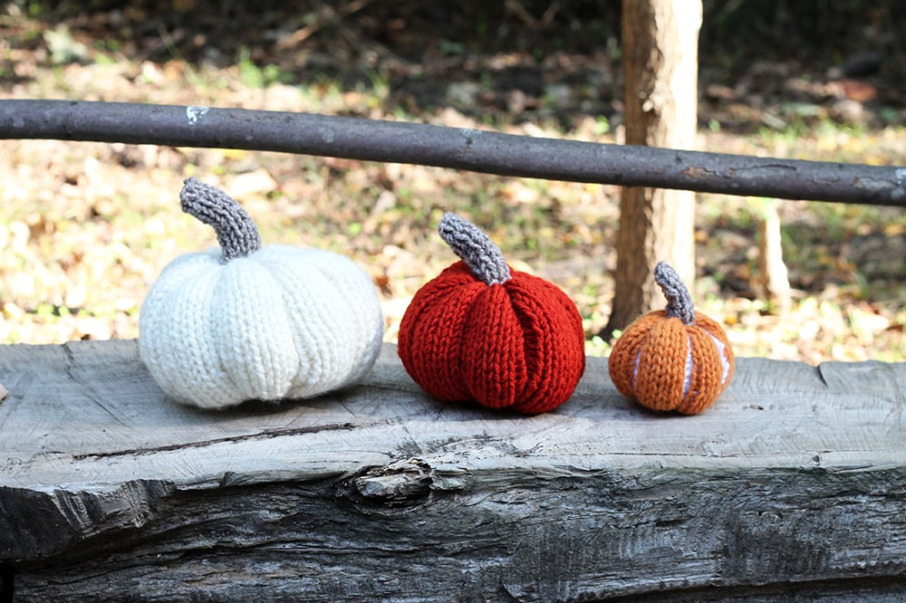 three knitted pumpkins on a wooden bench