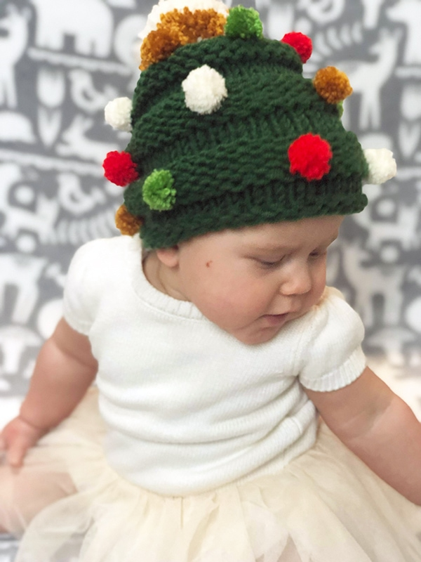 knit Christmas tree hat with coloured pom poms