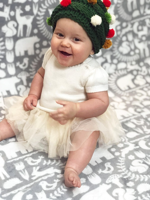 baby wearing a knitted Christmas tree hat