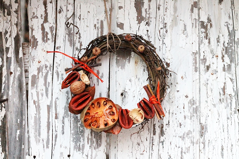 autumn door wreath with orange and red dried fruit and flowers