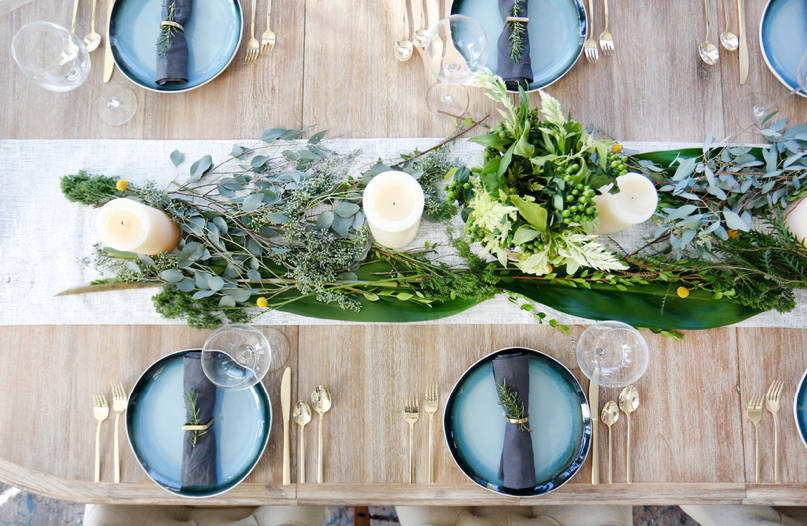 Thanksgiving table with fresh greens on a tablerunner