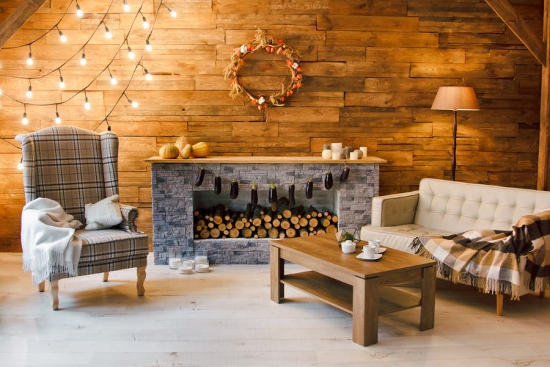 living room with wooden walls and log fireplace