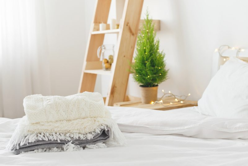 white bedroom with knitted blankets and mini Christmas tree