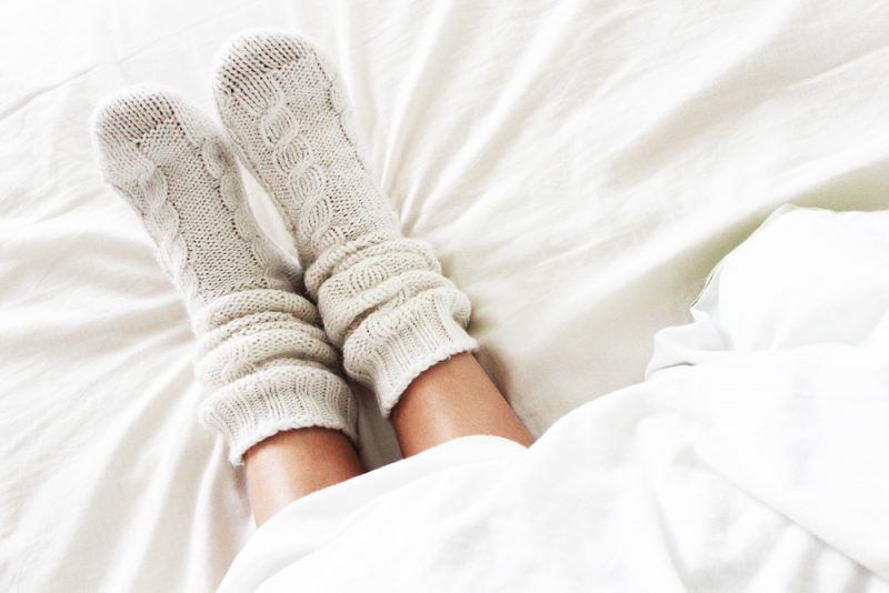 feet wearing knitted cable socks in bed