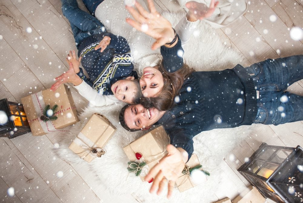 a family lying on the floor with Christmas gifts