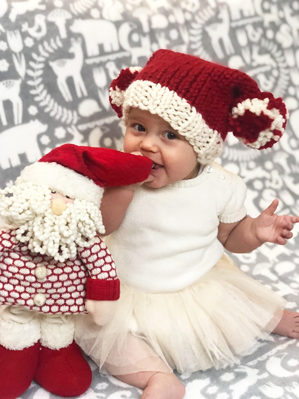 baby wearing a red and white Santa hat