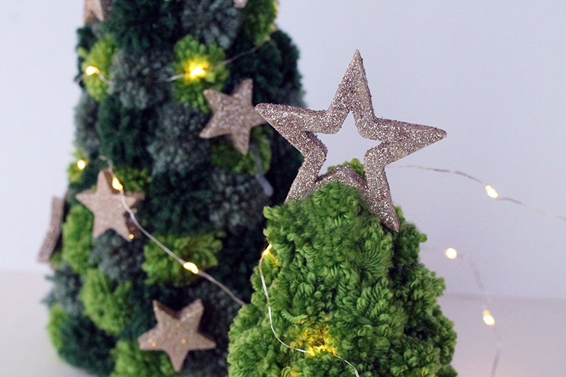 close up of pom pom Christmas tree with gold star decoration