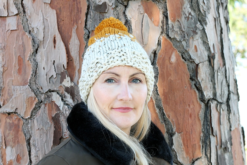 woman wearing a chunky knitted hat in wheat and mustard colours