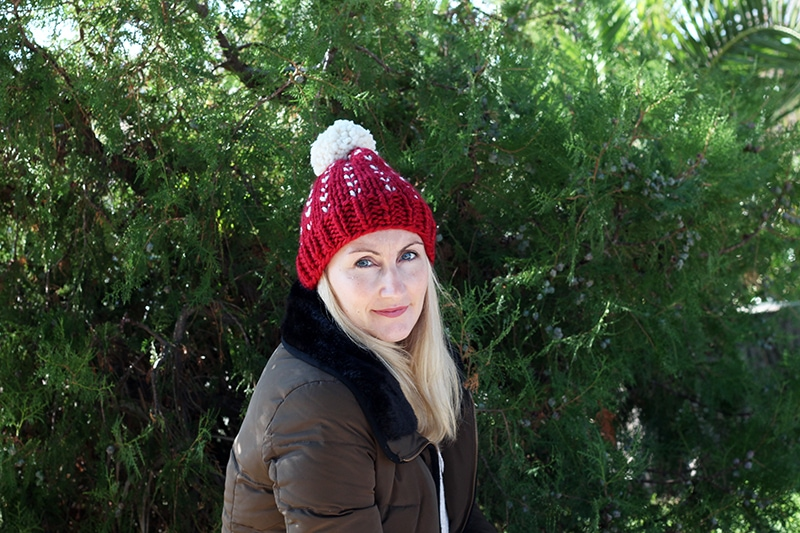 woman wearing a red and white knit hat with pom pom