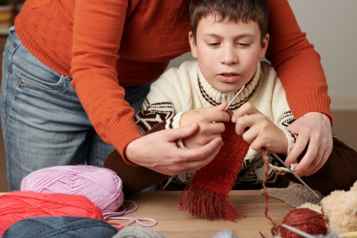 Boy learning how to knit
