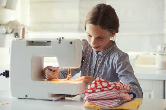 Little girl sewing on a sewing machine