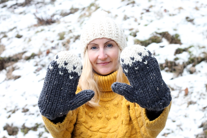 woman wearing chunky knit mittens in the snow