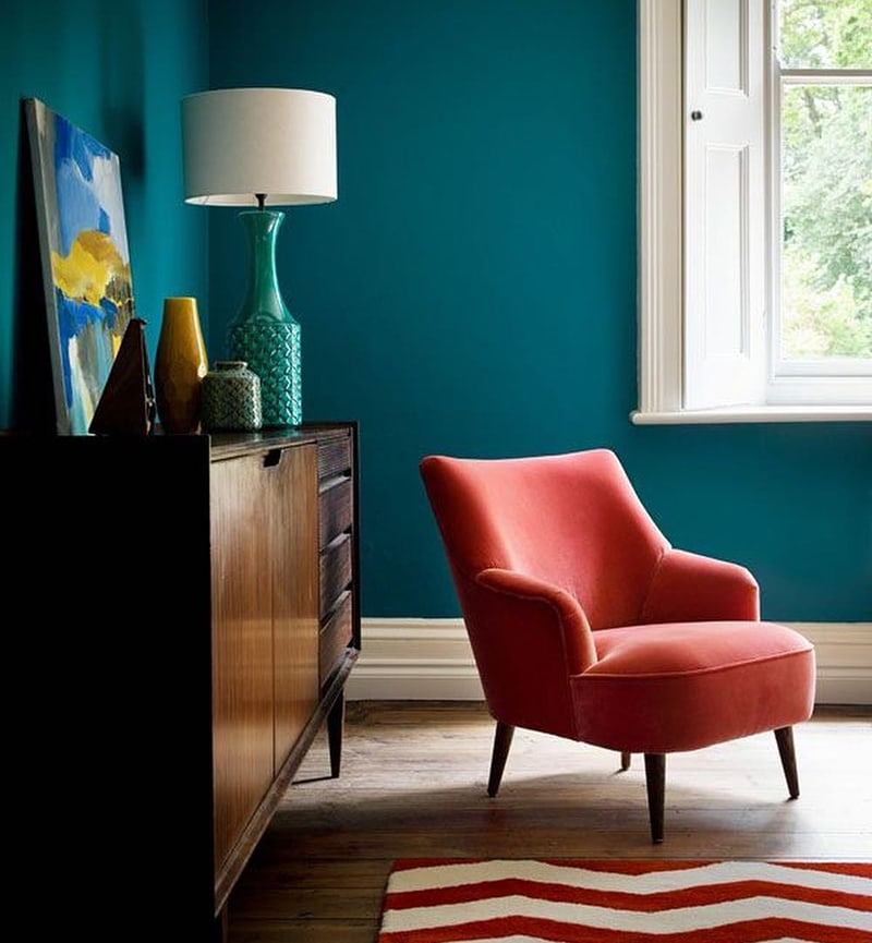 coral pink armchair in a jewel tone painted room