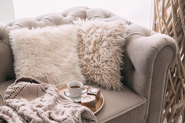 cozy faux fur pillows on a chair and a knitted blanket