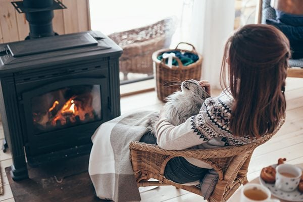 cozy log cabin fire and woman with cat