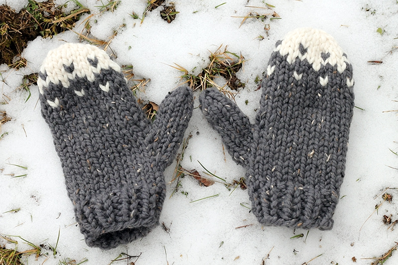 super bulky knit mittens lying in the snow