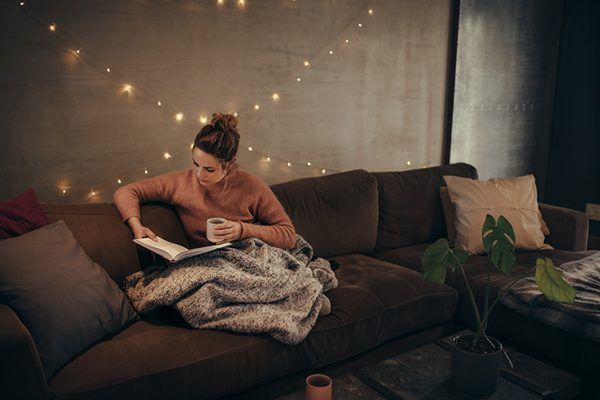 woman reading with knitted blanket