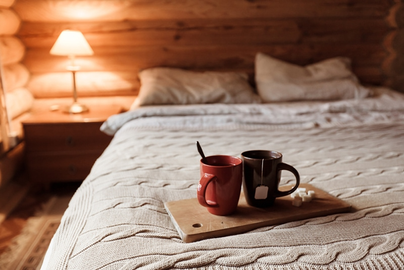 Cozy cabin bed with a knitted throw and coffee cups