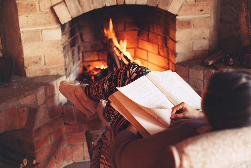 woman reading a book by an open fire