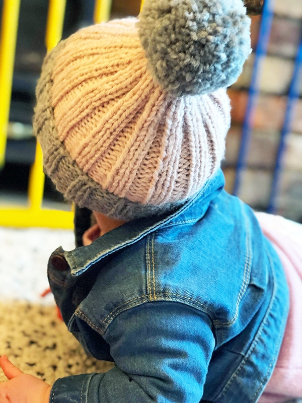 baby wearing a pom pom hat in grey and pink