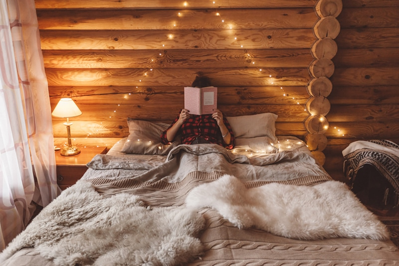 log cabin bedroom with knitted throws and fairy lights