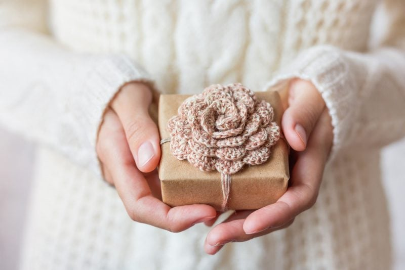 woman holding a box with a crochet flower decoration