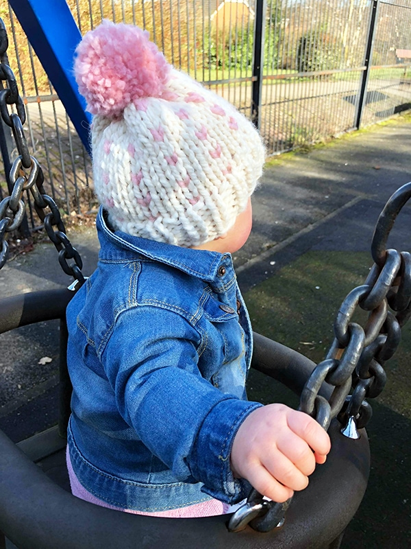 baby wearing a knitted pom pom hat