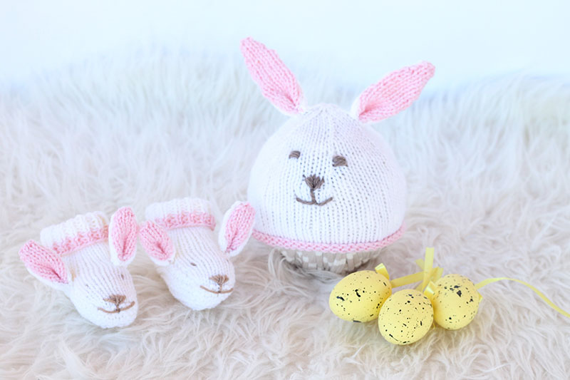 white knitted Easter bunny hat and matching bunny slippers for a baby