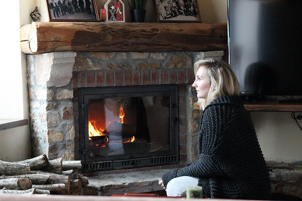 wearing a chunky knit cardigan by the fire