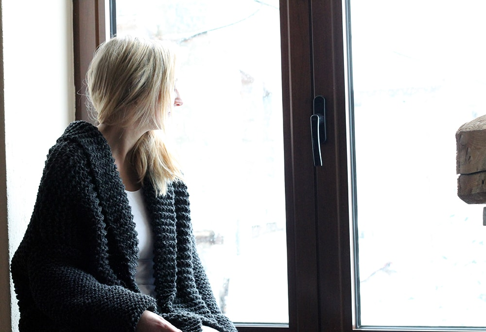 woman wearing an oversized knit cardigan and looking out of a window