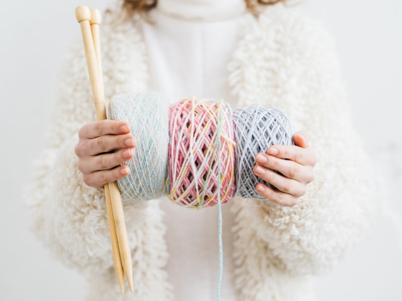 woman holding three skeins of yarn and knitting needles