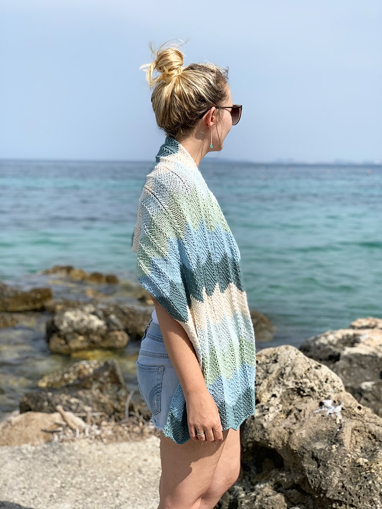 woman at the beach wearing a blue and green chevron patterned knitted shawl