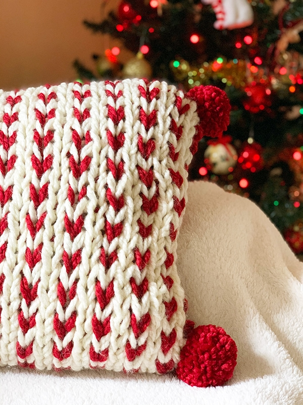 chunky knit pillow in red and white yarn with pom poms