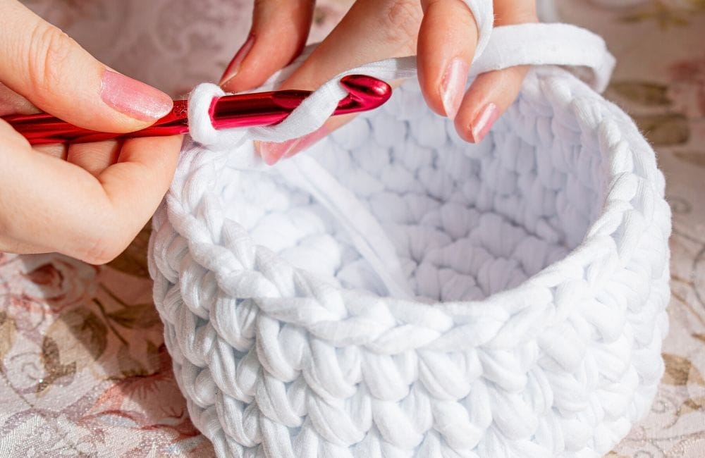 woman making a crochet basket