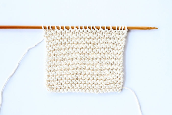 garter stitch example in white cotton on a knitting needle