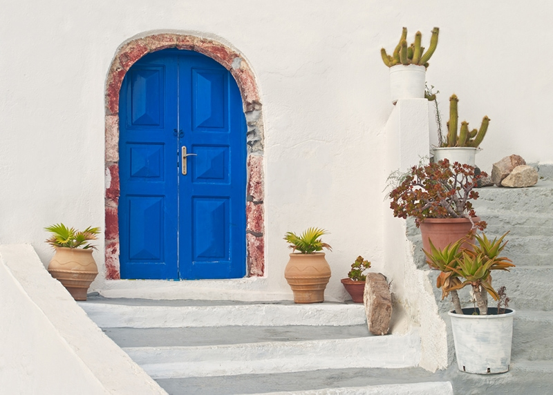 Greek style blue painted front door and white washed house