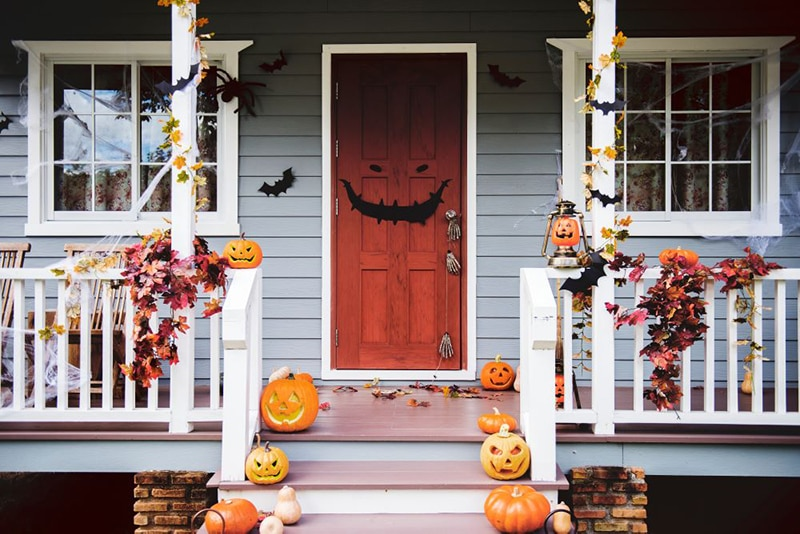 front porch decorated for halloween with carved pumpkins