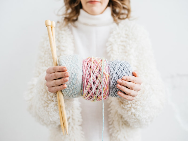 woman holding three skeins of yarn and wooden knitting needles