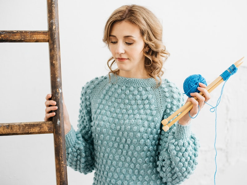 woman wearing a bobble knit sweater holding knitting needles