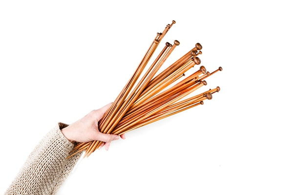 woman holding many wooden knitting needles
