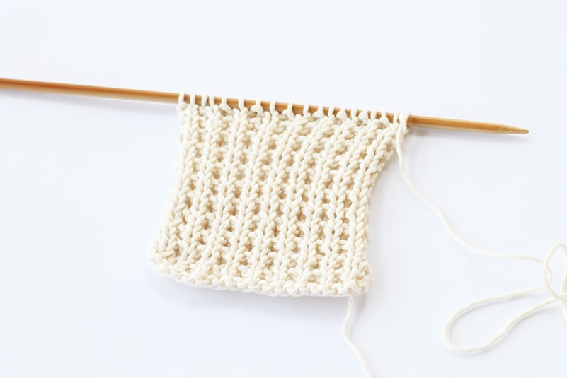 broken rib stitch in white cotton on a knitting needle