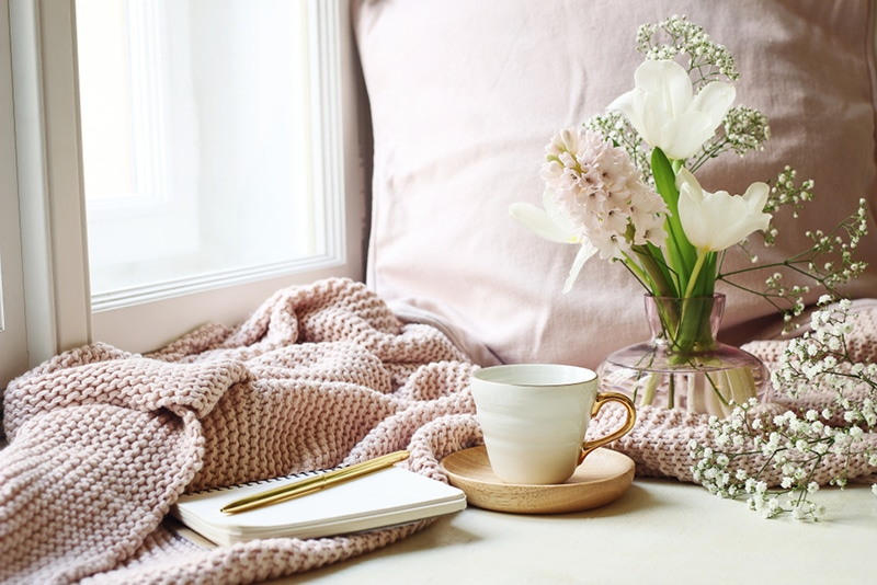 pink knitted blanket next to a tea cup and notebook