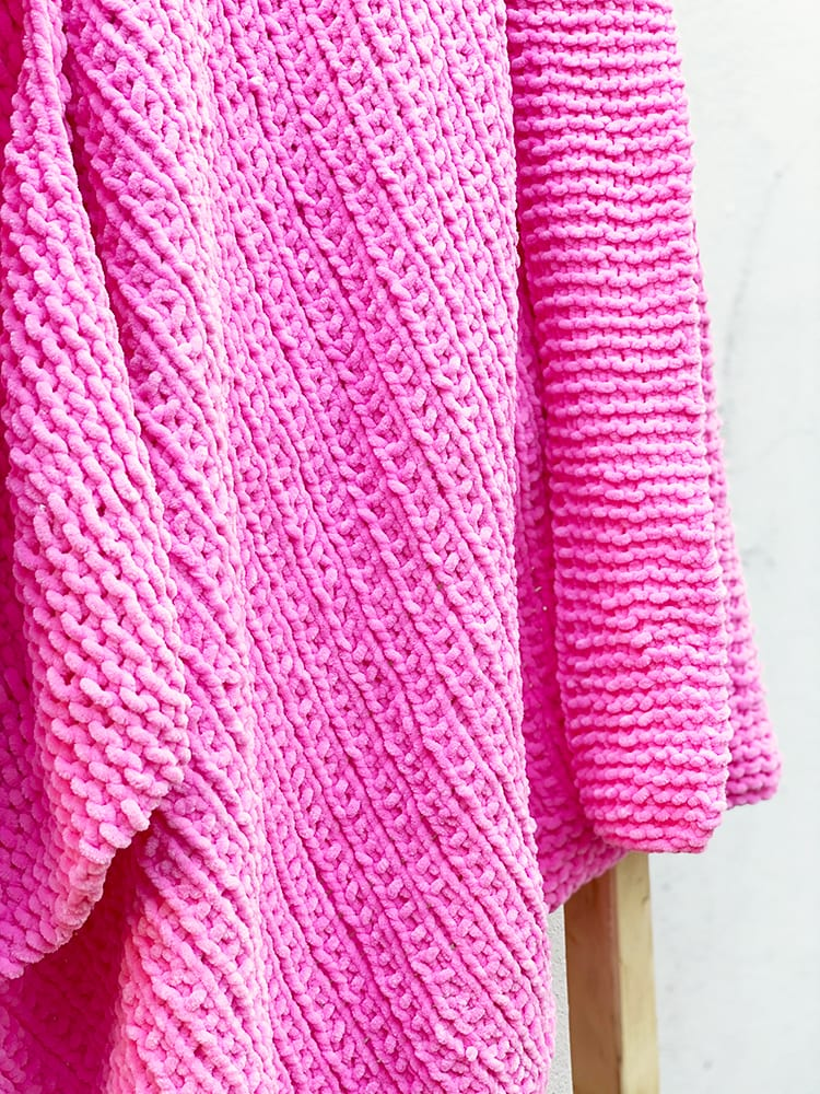 knitted baby blanket in pink yarn
