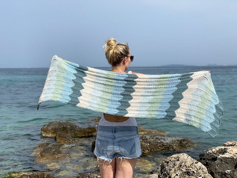 Girl holding a knitted shawl at the beach