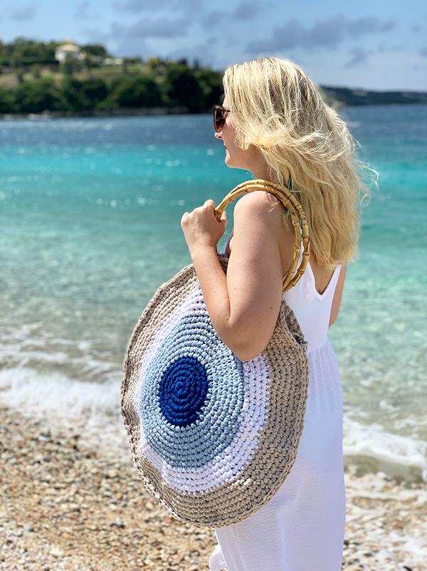 woman wearing a crochet circle beach bag with bamboo handles