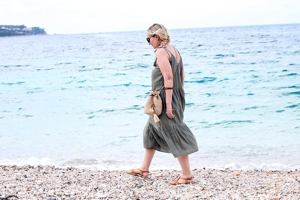 woman walking along the beach wearing a green dress and a crochet bucket bag