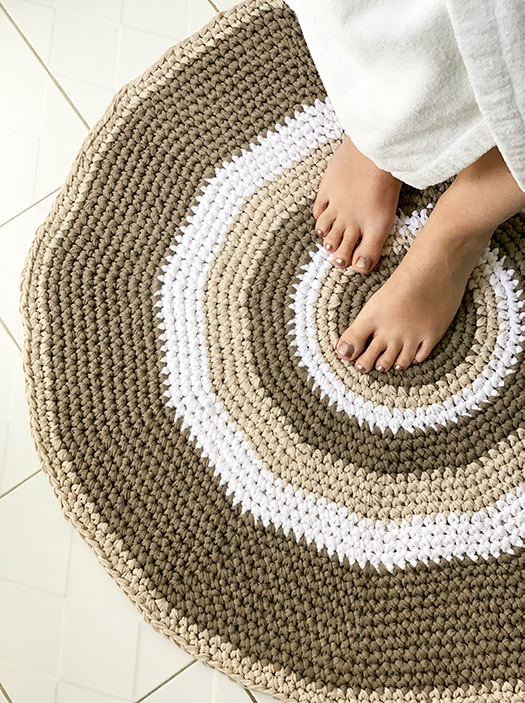 crochet circle rug in brown and white on a bathroom floor