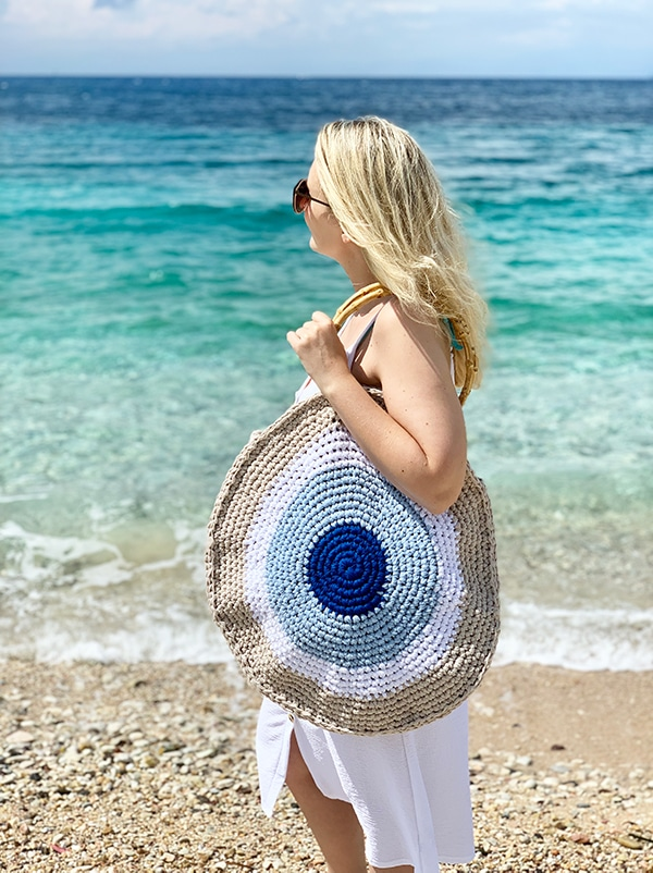 woman wearing a large crochet circle bag at the beach