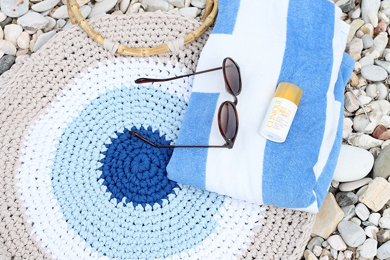 Bird's eye view of a crochet beach bag with sunglasses, suncream and a beach towel