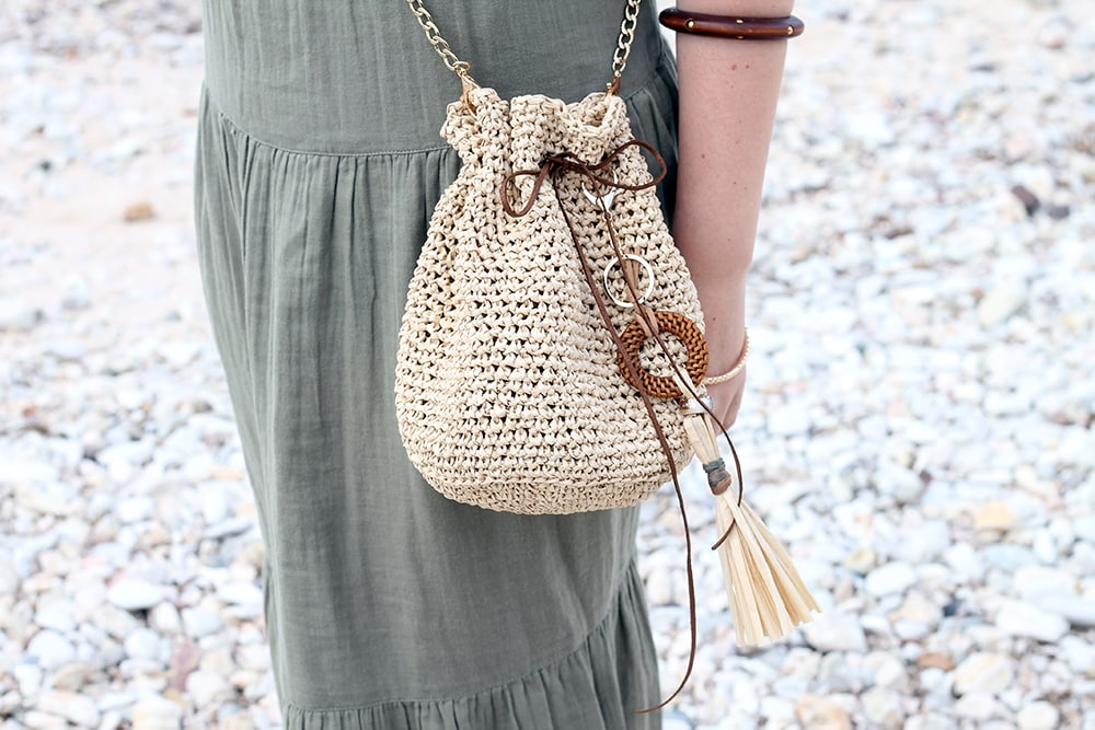 girl wearing a green dress and a cross body raffia drawstring bag at the beach